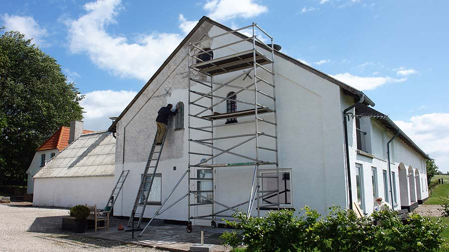 Man on scaffolds painting a house