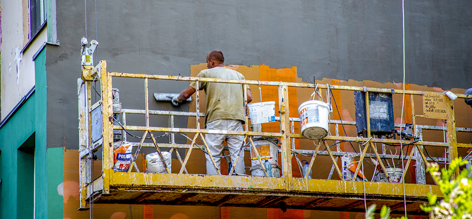 a worker perform plastering an exterior wall of the